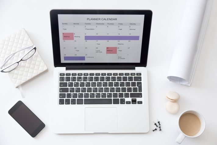 High angle view image of desk, planner calendar on laptop